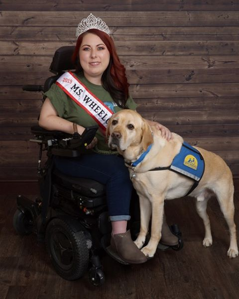 Lauren Taylor, Ms. Wheelchair Texas sitting in her wheelchair with her dog standing beside her.